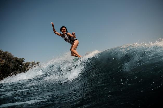 Donna castana sexy attiva che pratica il surfing a bordo giù l'acqua blu Foto Premium