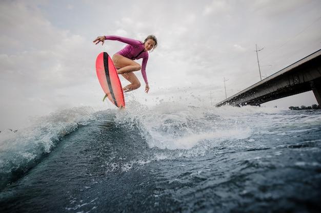 Donna esile attiva che salta sull'onda blu contro il cielo grigio Foto Premium