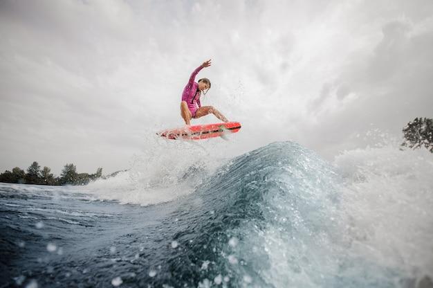 Surfista attivo della donna che salta sull'onda di spruzzatura blu contro il cielo Foto Premium