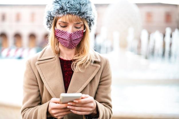 Donna dipendente con maschere protettive utilizzando l'app di monitoraggio sullo smartphone mobile Foto Premium