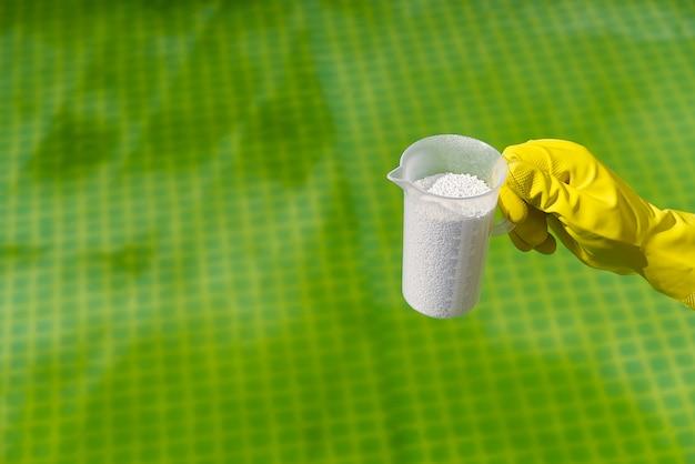 Aggiunta di polvere di cloro per la piscina per rimuovere le alghe e disinfettare l'acqua. concetto gonfiabile di cura della piscina. Foto Premium