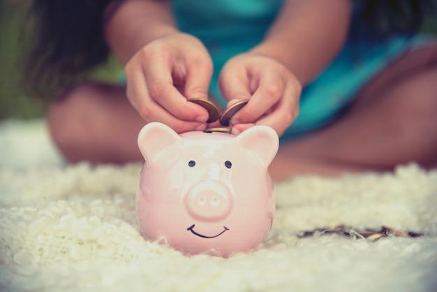 Mani adorabili dei bambini che risparmiano le monete in porcellino salvadanaio. felice investimento piccolo risparmio di denaro per il futuro della felicità. Foto Premium