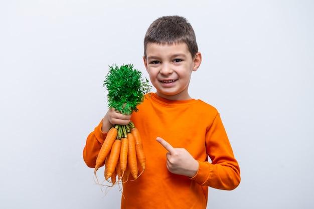 Adorabile bambino con carote. sani ortaggi biologici per bambini. ragazzo del bambino che tiene le carote in sue mani. Foto Premium