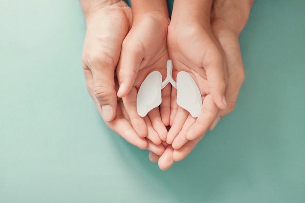 Mani del bambino e dell'adulto che tengono polmone, giornata mondiale della tubercolosi, giornata mondiale senza tabacco, virus corona covid-19, inquinamento atmosferico eco. concetto di donazione di organi Foto Premium