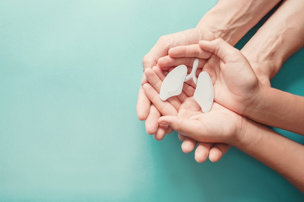Mani del bambino e dell'adulto che tengono polmone, giornata mondiale della tubercolosi, giornata mondiale senza tabacco, inquinamento atmosferico eco; concetto di donazione di organi Foto Premium