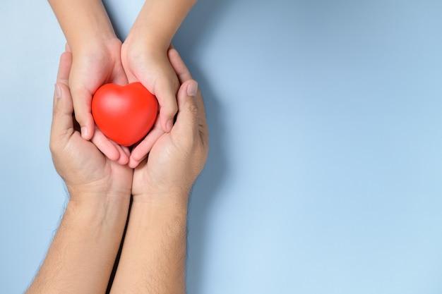 Mani di adulti e bambini che tengono cuore rosso isolato, assistenza sanitaria, amore e concetto di assicurazione familiare Foto Premium