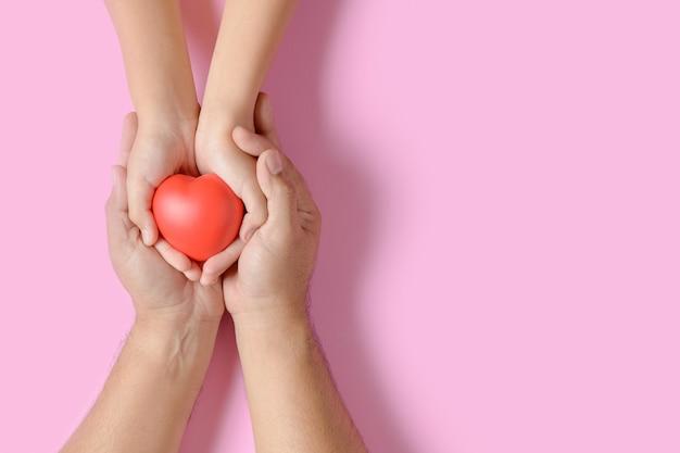 Mani del bambino e dell'adulto che giudicano cuore rosso isolato sul rosa Foto Premium