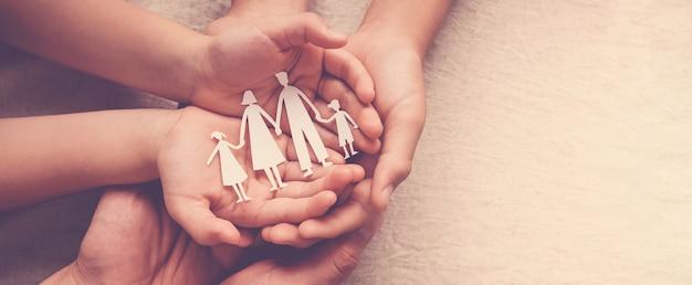 Mani di adulti e bambini che tengono il ritaglio di carta di famiglia, casa di famiglia, affido, sostegno dei senzatetto Foto Premium