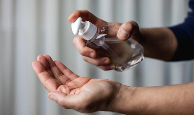 Uomo adulto disinfettando le mani con gel disinfettante Foto Premium