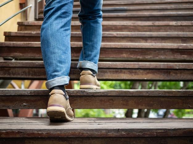 Uomo adulto che cammina sulle scale di legno Foto Premium