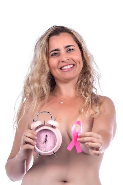Donna adulta che copre i seni con le mani che tengono il nastro rosa di consapevolezza del cancro al seno e un orologio, sopra un bianco. Foto Premium