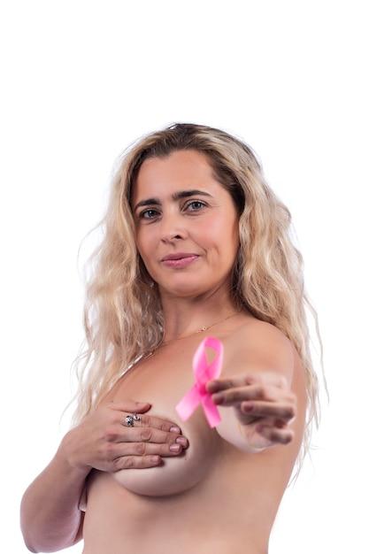 Donna adulta che copre i seni con le mani che tengono il nastro rosa di consapevolezza del cancro al seno, sopra un bianco. Foto Premium