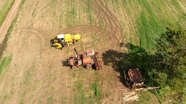 Vista aerea dal fuco di due mietitrebbiatrici e mietitrebbie agricole, stare su un ampio campo marrone tra l'albero verde solitario Foto Premium