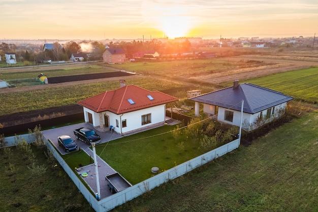 Vista aerea di case private in zona suburbana rurale al tramonto. Foto Premium