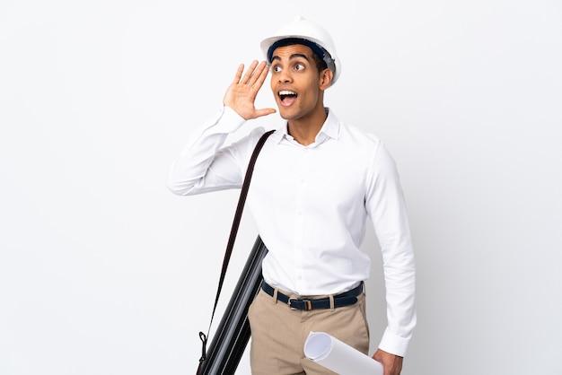 Uomo afroamericano dell'architetto con il casco e che tiene i modelli su bianco isolato Foto Premium