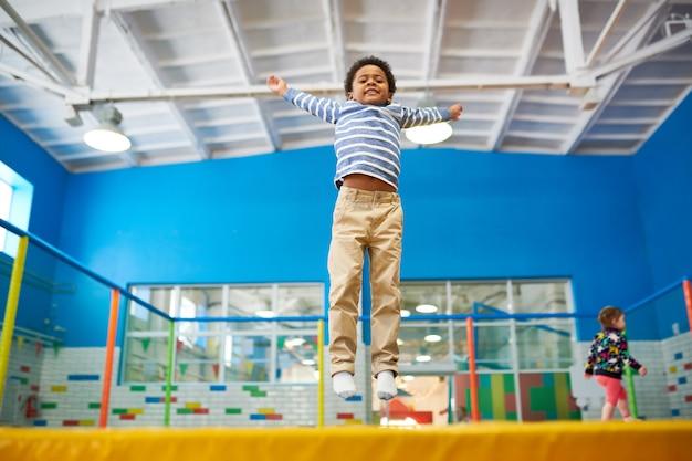 Ragazzo afroamericano che gode dei trampolini Foto Premium