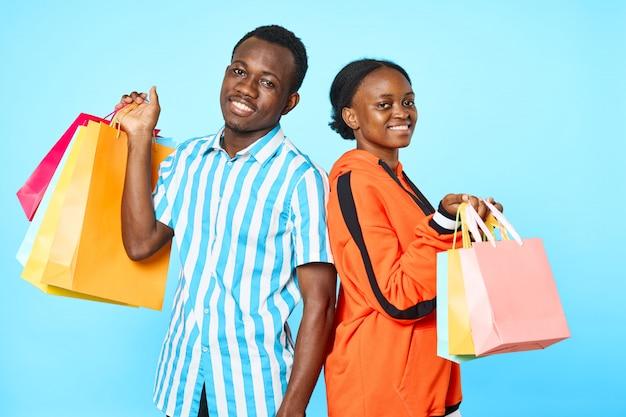Coppie dell'afroamericano che propongono con i sacchetti di acquisto Foto Premium