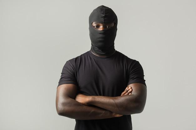Uomo africano in una maschera nera e una maglietta nera su un muro grigio Foto Premium