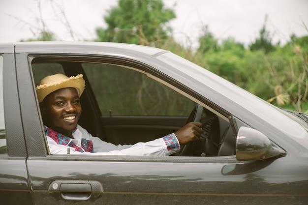 Autista africano dell'uomo che sorride mentre sedendosi in un'automobile con la finestra anteriore aperta Foto Premium