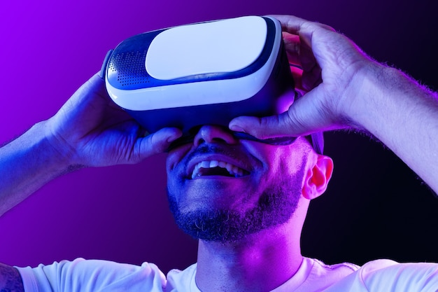 Uomo afroamericano che indossa occhiali vr in luce al neon su sfondo viola Foto Premium