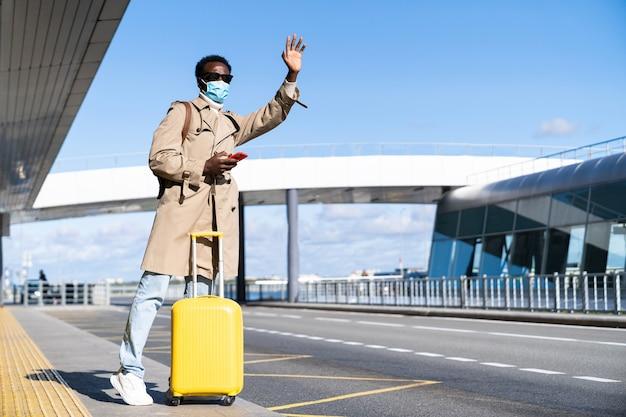 L'uomo millenario afro-americano con la valigia gialla si trova nel terminal dell'aeroporto, usa il telefono, chiama un taxi, alza la mano, indossa una maschera medica per proteggersi dal contatto con il virus dell'influenza, covid-19 Foto Premium