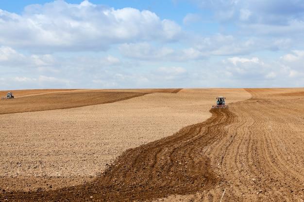 Il campo agricolo, che arato in un trattore preparando il terreno per la semina. primavera Foto Premium