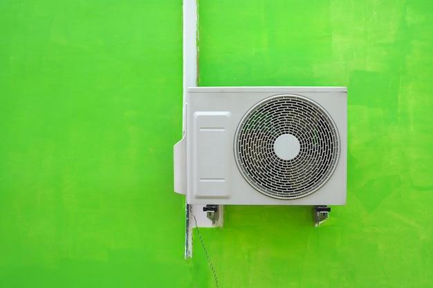 Compressore del condizionamento d'aria vicino ai precedenti verdi di struttura della parete Foto Premium