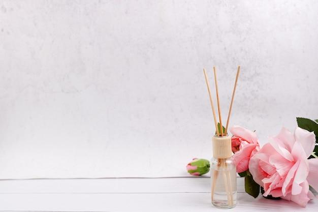 Deodorante per ambienti bastoni su fondo di legno bianco con rose rosa, copia dello spazio Foto Premium