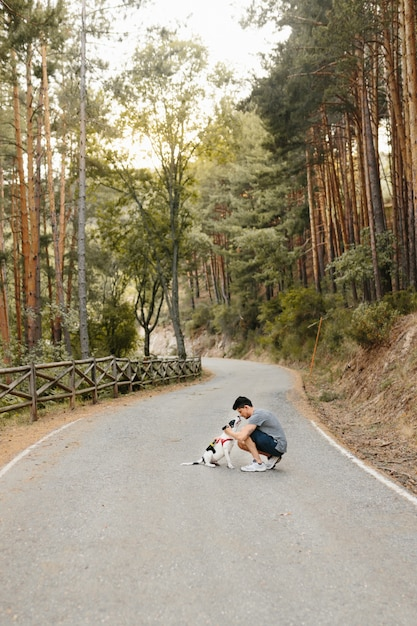 Solo uomo che bacia, abbraccia e accarezza il suo cane labrador bianco e nero della sua famiglia sulla strada nella pineta sotto la luce del sole di sera Foto Premium