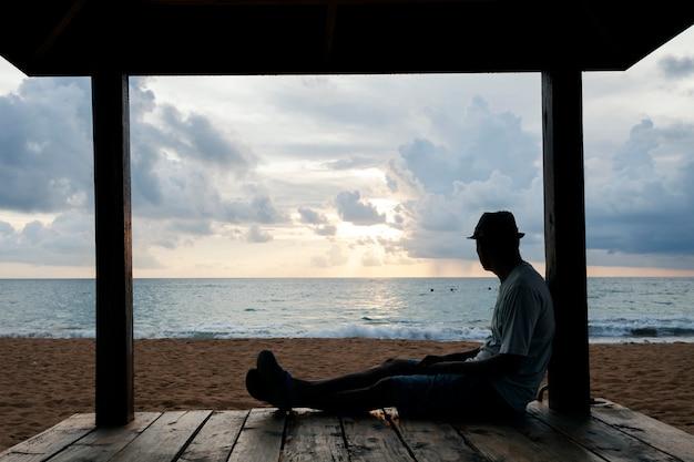 Uomo solo seduto sul lungomare in tempo di sera Foto Premium