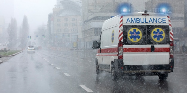 Un'ambulanza ha portato il paziente in clinica con le frecce accese. fuori tempo brutto, pioggia con neve bagnata. Foto Premium