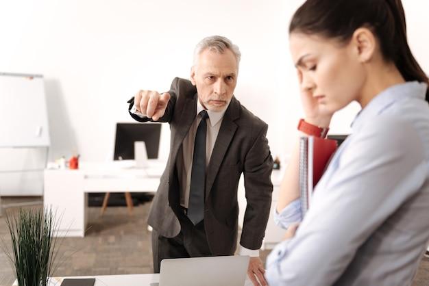 Capo arrabbiato che indossa un costume elegante rughe sulla fronte guardando il suo lavoratore Foto Premium
