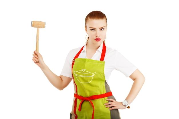 Casalinga arrabbiata con un martello di carne nelle sue mani Foto Premium