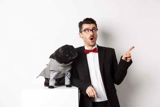 Concetto di animali, festa e celebrazione. giovane stupito e cane nero in costume fissano lo spazio della copia, in piedi contro il bianco Foto Premium