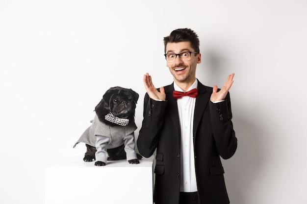 Concetto di animali, festa e celebrazione. bell'uomo e simpatico cane in costume si adatta a fissare sorpreso alla telecamera, reagendo all'offerta promozionale stupito, bianco. Foto Premium