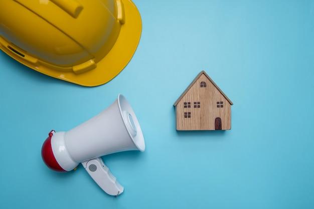 Annuncio e annuncio di relazioni pubbliche di fondo pubblicitario su edilizia, casa, casa e immobili con megafono e casco giallo Foto Premium