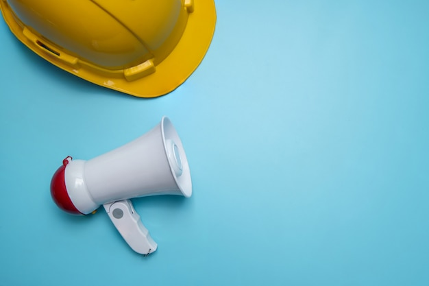 Annuncio e annuncio di pubbliche relazioni sulla parete pubblicitaria su edilizia, casa, casa e immobili con megafono e casco giallo sulla parete blu Foto Premium