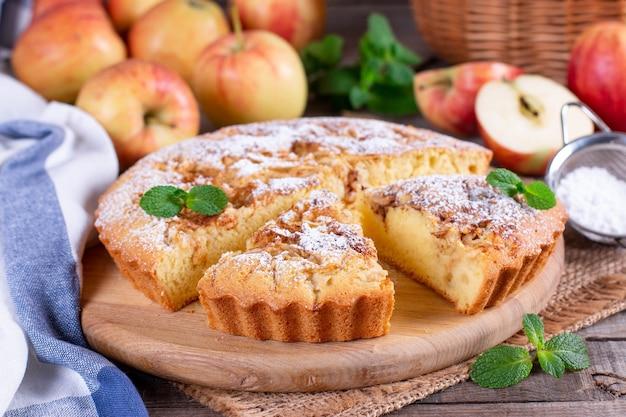 Torta di mele, pan di spagna, charlotte con mele su un tavolo di legno Foto Premium