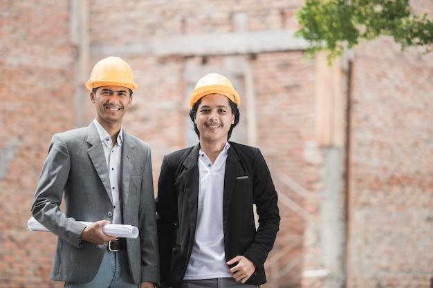 Architetto e costruttore in piedi davanti alla casa non finita Foto Premium