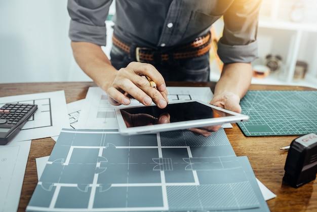 Uomo dell'architetto che lavora con la carta ed i modelli per il concetto di schizzo di piano architettonico della nuova costruzione di costruzione. Foto Premium