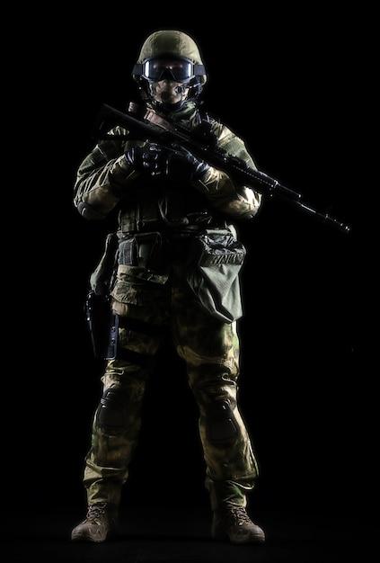 L'uomo armato in tuta mimetica sta con una pistola in mano. tecnica mista Foto Premium