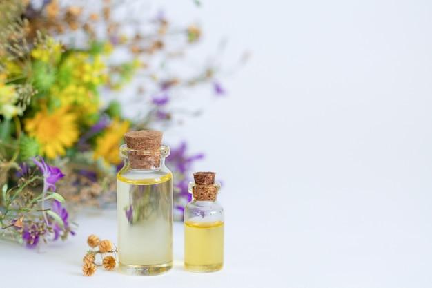 Bottiglie di olio essenziale di aromaterapia con erboristeria naturale, erbe curative e fiori sul tavolo bianco. spazio per il testo Foto Premium