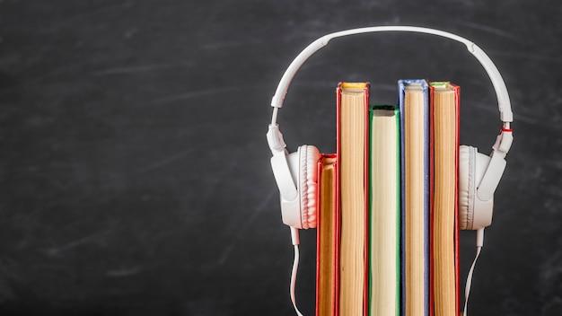 Disposizione dei libri con le cuffie con lo spazio della copia Foto Premium