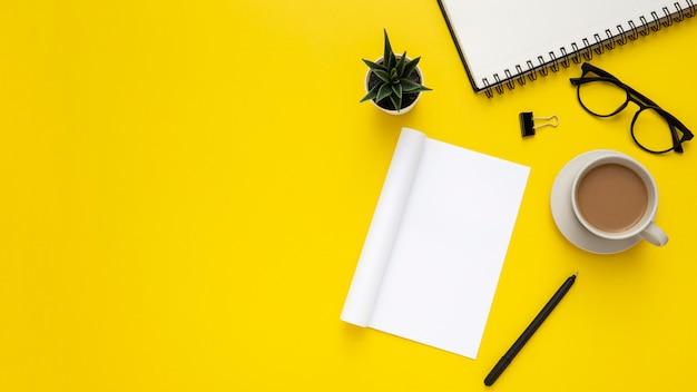 Disposizione degli elementi dello scrittorio con il blocco note vuoto su fondo giallo Foto Premium