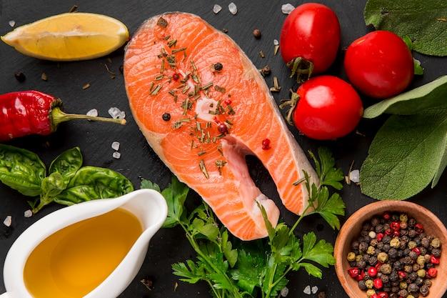 Disposizione di verdure e salmone con olio Foto Premium