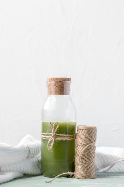 Disposizione con bottiglia di frullato verde Foto Premium