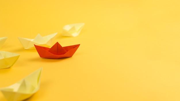 Disposizione con barche di carta su sfondo giallo e copia spazio Foto Premium