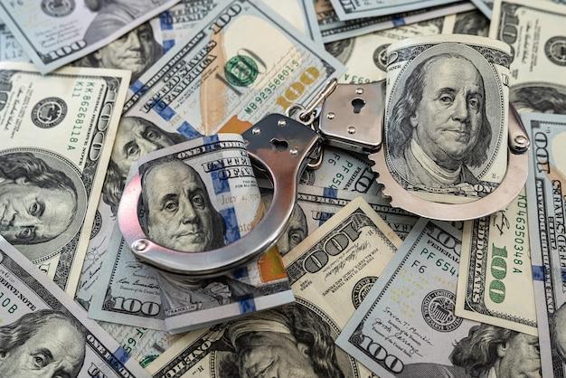 Arresto di criminali. manette in metallo su banconote da cento dollari Foto Premium