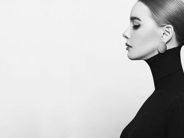 Ritratto d'arte di una donna bella ed elegante con un dolcevita nero e gioielli in oro Foto Premium
