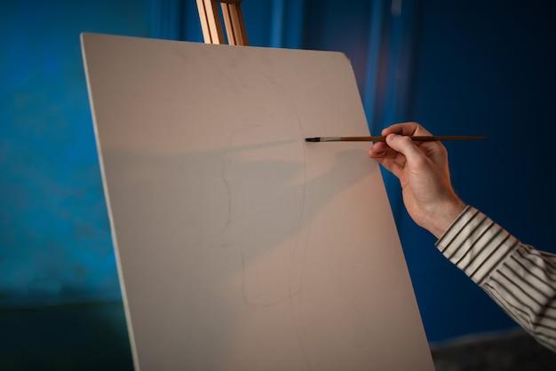 Artista con tavolozza e pennello davanti al cavalletto Foto Premium